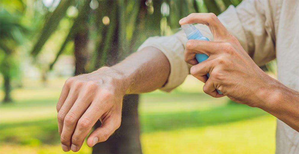 Mann trägt Mückenschutz auf